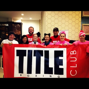 Running Team from Title Boxing Club with banner before a Tulsa 5k